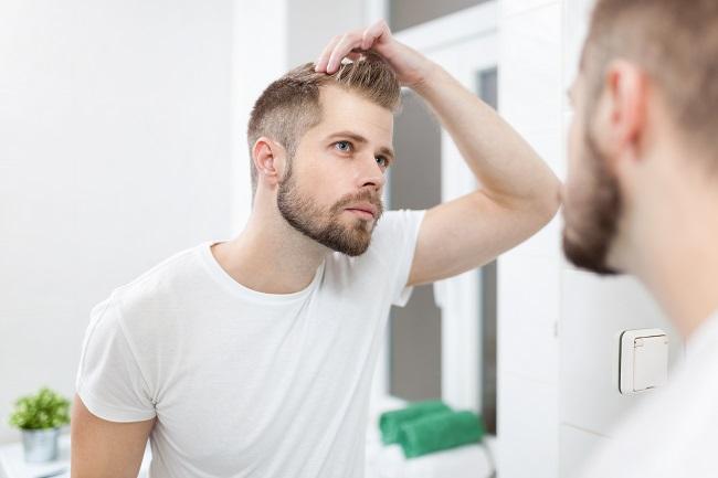 Hübscher unrasierter Mann, der vor dem Spiegel im Badezimmer seinen Haarausfall gutachtet.