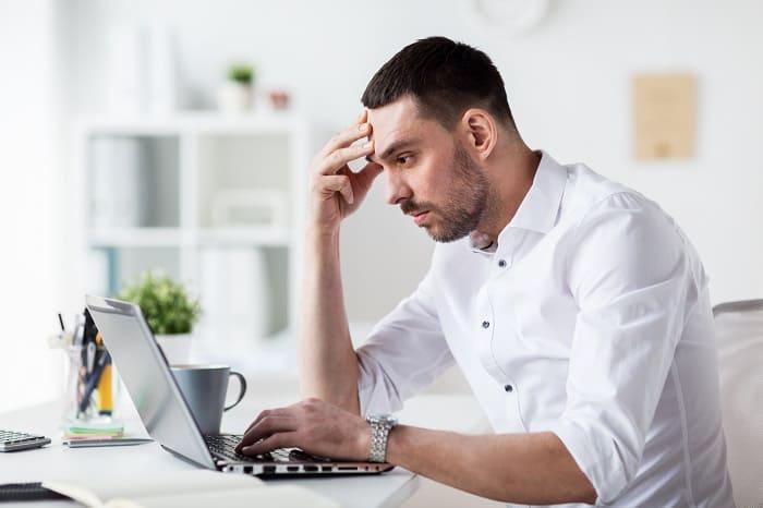 Haarausfall durch Stress - Gestresster Mann arbeitet im Büro