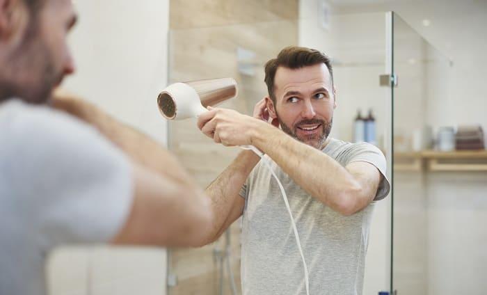 Junger Mann fönt seine Haare