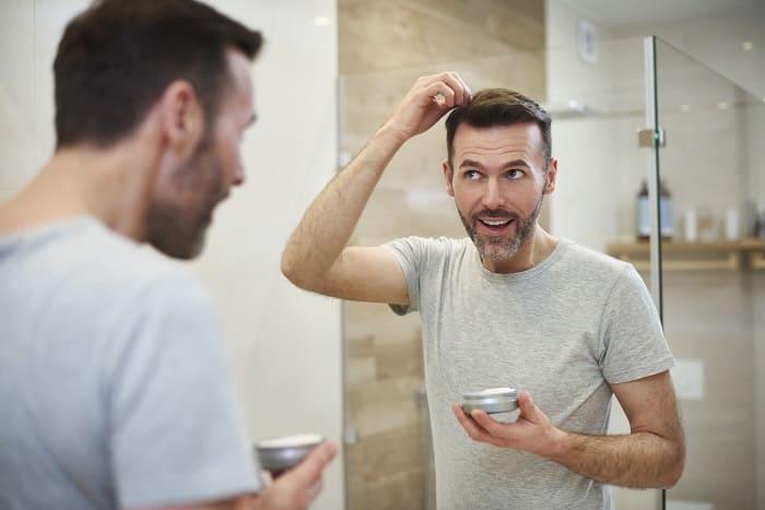 Junger Mann pflegt seine Haare.