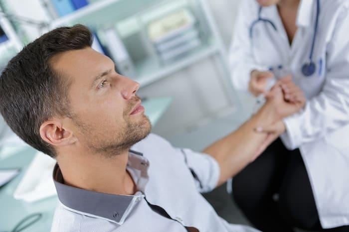 Arzt nimmt Blut von einem Patienten