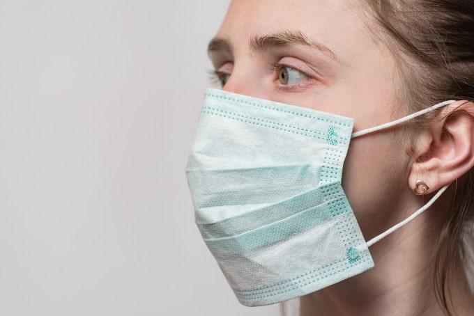 Junge Frau trägt Atemschutzmaske, die man hinter die Ohren befestigt