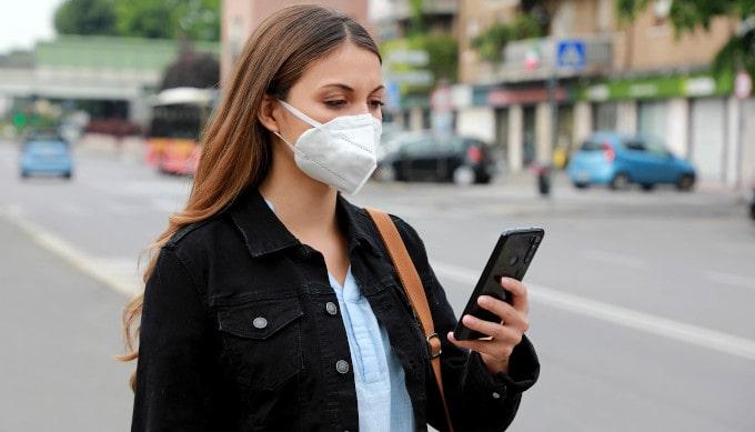 Junge Frau trägt eine FFP2 Maske und guckt dabei auf Ihr Handy
