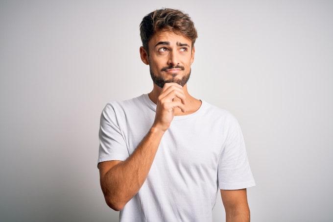 Junger Mann mit Hand am Kinn steht vor weißem Hintergrund und denkt über eine Frage nach